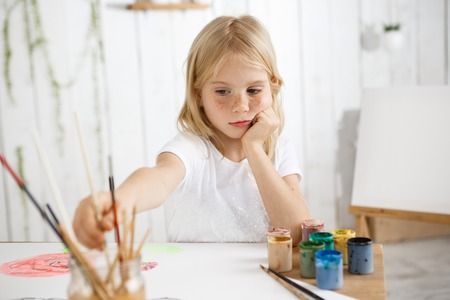 Creative seven-year-old girl busy painting watercolors, sitting at the table and putting her elbows on the table, rested her head in her hands, thinking about her picture. Little female child with blonde hair and freckles wearing white t-shirt, sitting at Stock Photo