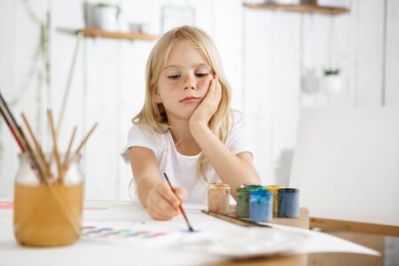 children painting: Portrait of little girl with blonde hair and freckles sitting at the desk and, putting her elbow on the table, thoughtfully looking at her picture. Horizontal, isolated shot