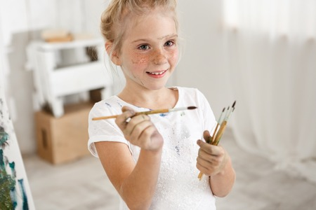 Close-up portrait of blonde cute European little girl with paint on her freckled face and hair bun smiling with all her teeth holding a bunch of brushes in her hands. Cheerful girl messed up her white t-shirt, enjoying art activities.
