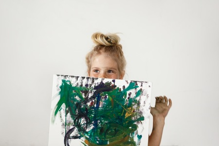 children painting: Small European blonde girl with blue eyes and hair bun holding colourful picture and hiding her face. Happiness and joy of little girl is so charming. Kids` art activities.
