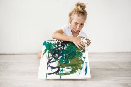 children painting: Little blonde female child with hairbn and freckles wearing white t-shirt occupied with her picture. Cute, adorable girl sitting on a floor with colourful canvas on her knees.