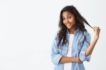 Studio shot of cute dark-skinned woman playing with her long wavy hair, glowing face and gentle smile rejoicing her beauty. Cheerful woman dressed casually having pleased and flirting expression. Facial expressions Stock Photo