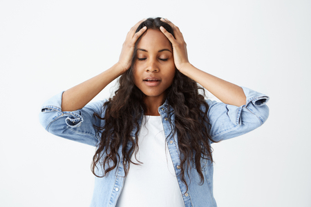 Afro-American female student with long wavy hair casually dressed feeling stressed, keeping hands on her head, with closed eyes in frustration and despair after she made serious mistake.