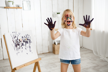 Playful and laughing blonde girl having fun, enjoying art activities. European female child wearing white t-shirt standing behind easle with her picture on it showing how dirty her hands are.