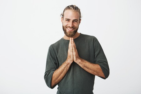Portrait of expressive handsome man with stylish hair and beard smiling, pressing palms together in front of him asking his girlfriend to forgive after stupid joke.