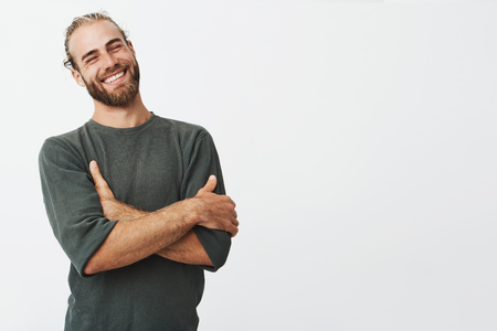 Attractive swedish man with stylish hair and beard laughs at funny story from friend with crossed hands and closed eyes. Stock Photo