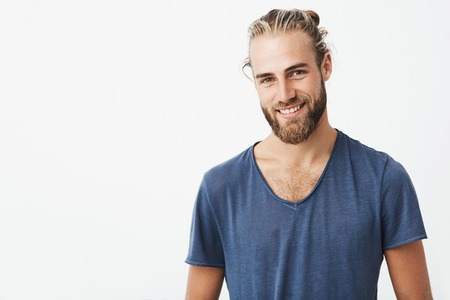 Portrait of good-looking nordic unshaven man with fashionable hairdo posing for magazine article
