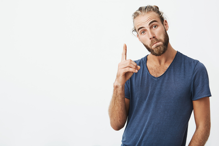 pursuing: Beautiful swedish guy with good-looking hairstyle and beard looking at camera with funny face expression, pursuing lips and pointing upside with finger. Copy space. Stock Photo