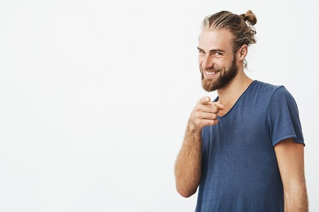 Portrait of good-looking bearded man with great hairdo pointing with index finger in camera and brightfully smiling. Copy space