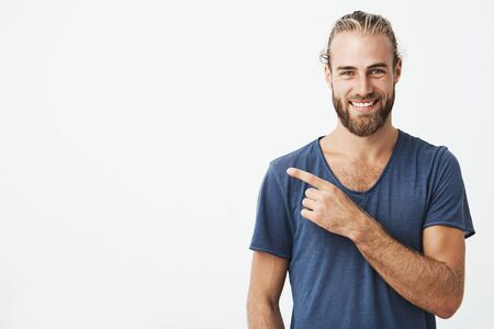 Happy beautiful bearded guy with good-looking hairstyle looking at camera, smiling and pointing aside with hand. Copy space. Standard-Bild