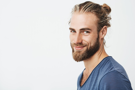 Close up portrait of handsome manly guy with beard posing in three quarters, looking in camera and happily smiling. Lifestyle concept. Stock Photo