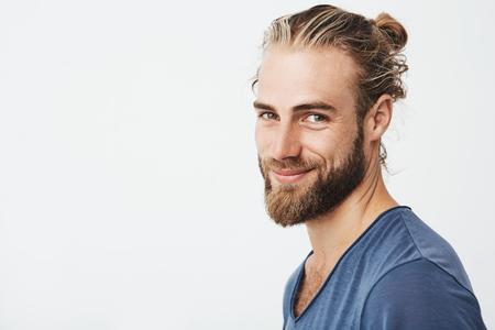 Feche o retrato do bonitão viril com barba posando em três quartos, olhando na câmera e sorrindo feliz. Conceito de estilo de vida. Foto de archivo