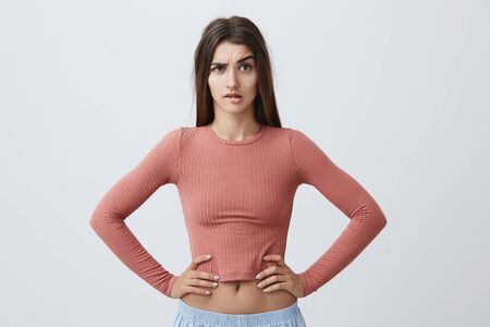 Portrait of young unhappy caucasian girl with dark long hair in trendy pink top and sporty blue trousers looking in camera with angry expression, holding hands on waist, seeing her boyfriend with other girl on street. Stock Photo