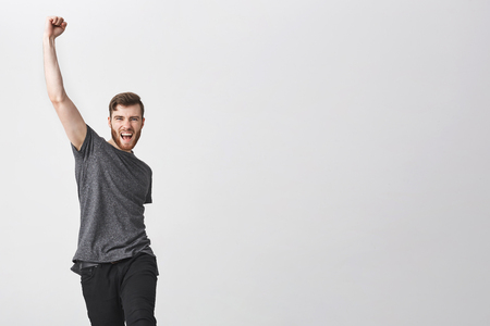 Dinamic portrait of beautiful manly bearded man with dark haie and arm tattoo in casual grey t shirt raising hand in jump with happy and excited face expression. Guy happy to know his fave hokey team won in match. Stok Fotoğraf