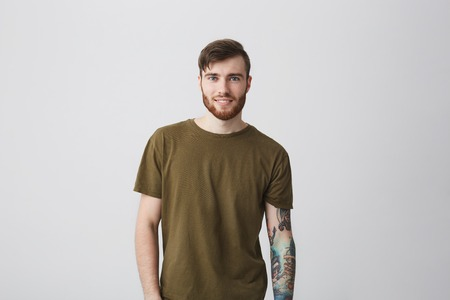 Portrait of attractive bearded caucasian man with tattoo on arm and stylish hairstyle wearing casual green t-shirt, looking in camera with happy and satisfied expression. Positive emotions. Stock Photo - 88690063