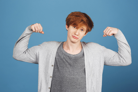 sweatshirt: Portrait of young good-looking guy with ginger hair in casual gray clothes playing muscles, looking in camera with unsure and confused expression, feeling uncomfortable.