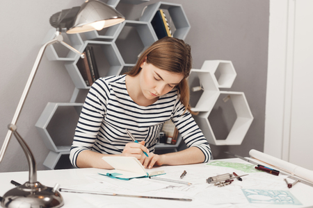 Close up of young good-looking european female freelance designer with dark hair in striped clothes sitting at table in office, writing down project mistakes in notebook to discuss them on meeting. Stock Photo