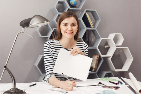Close up portrait of young cheerful good-looking female freelance architect with dark hair in striped shirt smiling, showing white paper list in camera, copy space for your advertisement.