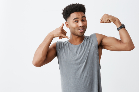 So call me maybe. Close up of young cheerful dark-skinned male with afro haircut in grey shirt showing muscles, making phone sign with hand, looking in camera with flirty expression Stock Photo