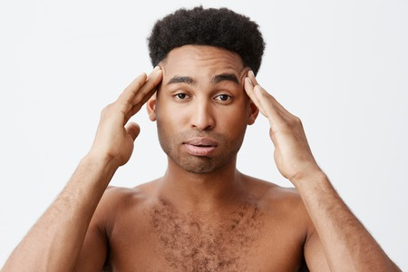 Negative emotions. Man having headache after partying all night. Close up of young dark-skinned male with afro hairstyle without clothes massaging head with hands.