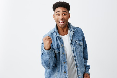 Yeah. Finally. We did it. Cheerful young attractive black-skinned man with afro hairstyle in denim jacket holding hand in front of him with excited expression, being happy he won lottery.