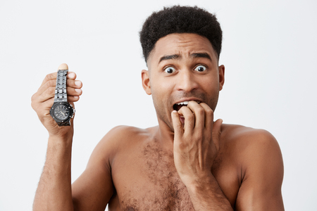 Close up portrait of attractive sexy black skinned american guy with curly hair without clothes holding hand watch in hand, holding hand near mouth, looking in camera with frightened expression.
