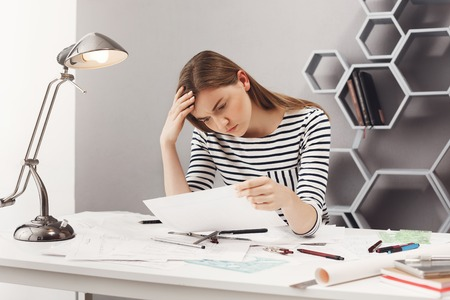 Portrait of beautiful young unhappy female engineer sitting at white table in cosy coworking space, looking at papers with upset expression being sad after finding mistake in blueprints. Stock Photo