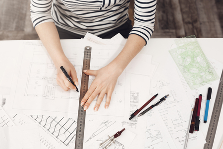 Close up portrait of professional young beautiful female architect in striped clothes, doing her drawings with ruler and pen, working with interest on new project.