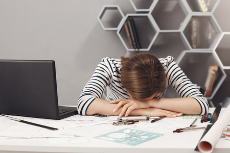 Job occupation and overwork. Close up of tired young good-looking engineer girl with dark hair in striped clothes lying on hands in office, suffering from headache after long work day. Stock Photo