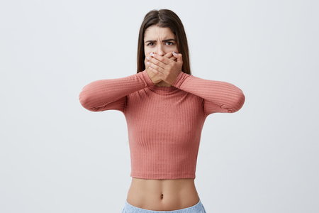 I wont say anything. Portrait of handsome charming young caucasian girl with brown long hair in pink top and blue trousers clothing mouth with both hands in frightened look. Body language.