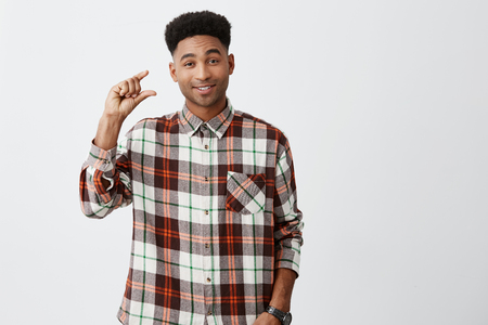 A little bit. Portrait of young good-looking dark-skinned funny guy with afro haircut in checkered shirt smiling, gesticulating with hands, looking in camera with sarcastic expression.