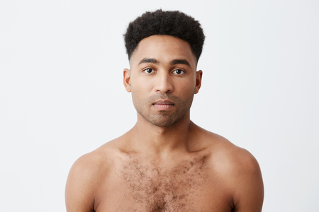 Waist up photo portrait of serious black-skinned mixed race african man with curly dark hair without clothes looking in camera with relaxed face expression. Stock Photo