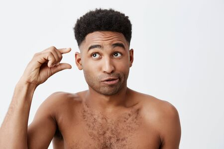 Portrait of funny dark-skinned american guy with curly hair and without clothes looking aside with silly and cynic expression, gesticulating with hand. Peoples emotions.