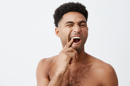Young funny good-looking afro american male with curly hair without clothes picking in teeth looking at mirror with mean expression taking bath in morning. Stock Photo
