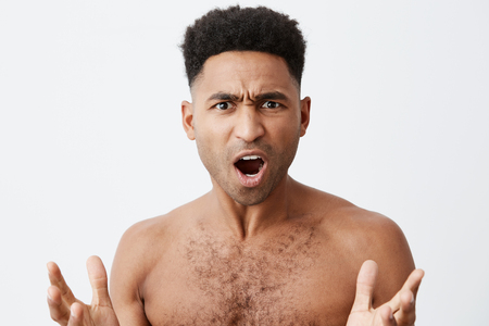 What the heck. Close up of beautiful black-skinned man with curly hair without clothes spreading hands with confused expression, when his favourite football team losing match