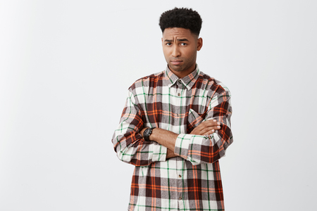 Portrait of unhappy young attractive black-skinned man with curly hair in casual checkered shirt crossing hands, looking in camera with offended expression after argue with girlfriend.
