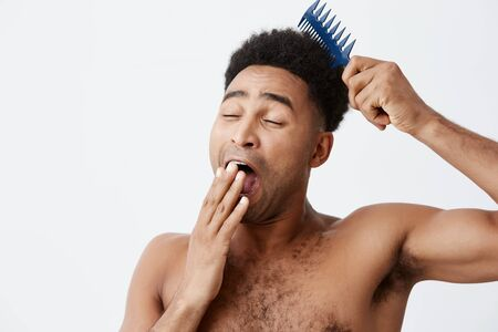Lazy morning. Portrait of funny good-looking afro american male with curly hair without clothes clothing mouth, yawning trying to comb hair in morning. White background