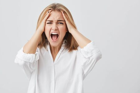Photo of disappointed woman with blonde hair holding her hands on temples frowning face having wide opened mouth screaming in despair and terror. Stock Photo
