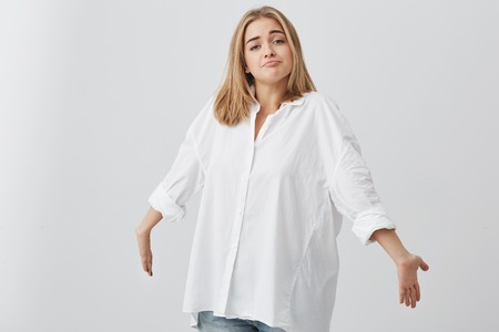 Blonde confused caucasian female in white shirt shrugging shoulders, stretching arms forward, staring at camera with questionable and clueless look, saying I dont know. People and emotions concept.