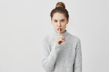 Hush! Headshot of caucasian woman holding index finger on lips. Female receptionist with dark hair tied in bun asking to keep quiet saying shh over white background. Silence concept