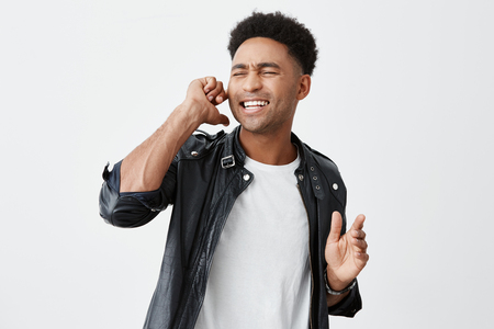 Positive emotions. Close up portrait of mature beautiful dark-skinned male student plugging ear with finger, closing eyes, singing in karaoke his favorite song. Stock fotó