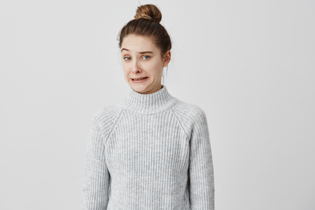 Caucasian girl with brown hair in bun posing with facial expressions of disgust. Female 20s making face meaning dislike and non-acceptance. Human reactions concept Stock Photo
