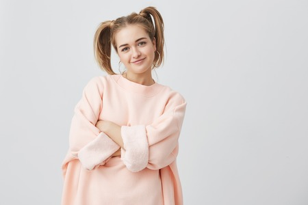 Stylish, trendy, pretty girl in pink long-sleeved sweatshirt with two ponytails and big round earing posing against gray background, keeping arms folded. Girl smiling, expressing positive emotions.