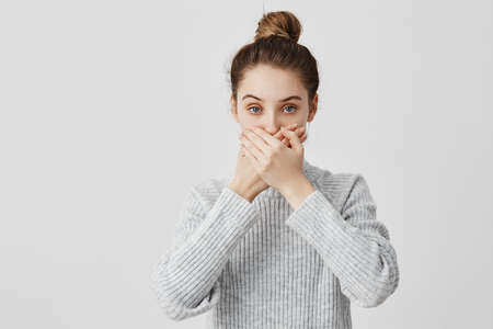 Brunette female 30s covering mouth with both hands keeping silence. Faithful lady friend promising not to tell secrets being trustworthy. People, attitude concept Stockfoto