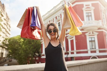 Selective focus. Positive emotions. Portrait of young beautiful dark-haired woman in sunglasses and black clothes holding colorful shopping bags under head with happy and excited face expression.