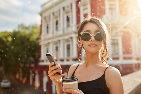 Summer days. Close up portrait of attractive skinny feminine caucasian woman with dark hair in tan-glasses and black dress, waiting for boyfriend that being late for date, chatting with friend by smartphone, drinking coffee, looking in camera with calm expression.
