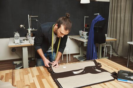 Mature creative handsome dark-haired caucasian male fashion designer in black suit cutting out clothes parts from fabric with scissors, spending evening in studio.