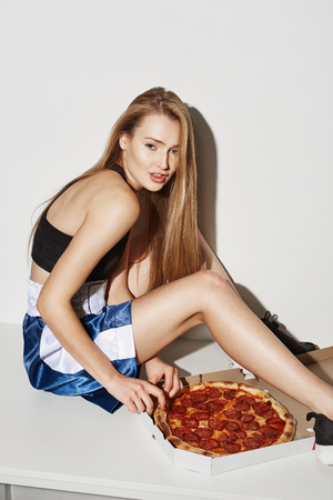 Vertical portrait of attractive young woman with blond hair, sitting on table,looking in camera with satisfied expression going to try pizza.