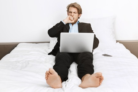 Portrait of sleepy attractive mature company director lying in bed, closing mouth with hand with hand while yawning, lazy working on laptop.