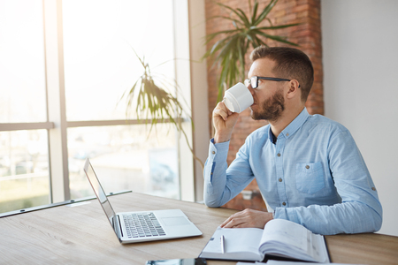 Close up of adult unshaved dark-haired caucasian male businessman in glasses sitting in office, looking aside in window with calm expression, drinking coffee, relaxing after hard work.
